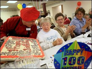 Chef Marshall Goldstein, left, presents a homemade birthday cake to Franciscan Sister Juliana Sienko.