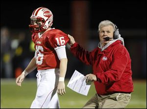 Eastwood head coach Jerry Rutherford gives instructions to QB Jake Schmeltz (16).