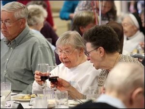 Helen Julkowski, 88, right, cheers with her biological sister, Franciscan Sister Juliana Sienko, center.
