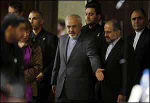 Catherine Ashton, the European Union's foreign policy chief, second from left, and Iranian Foreign Minister Mohammad Javad Zarif, center, arrive at a press conference at the end of the Iranian nuclear talks today in Geneva.