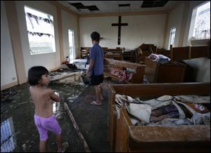 Residents look at bodies brought inside a damaged chapel.