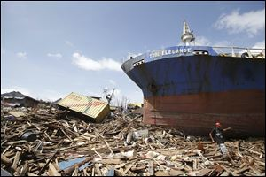 A survivor walks by a large ship that was washed ashore by strong waves caused by Typhoon Haiyan in the Philippines.