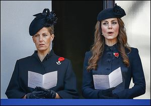 Britain's Catherine, the Duchess of Cambridge, right, and Sophie, the Countess of Wessex, sing from a balcony during the service of remembrance.