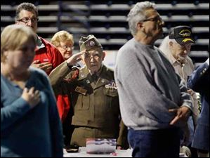 World War II veteran Guadalupe Flores, center, saluting as Taps are played at the conclusion of the ceremony.