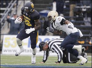 A ref is knocked to the ground as UT's David Fluellen is chased by Navy's Lonnie Richardson during game at the Universi