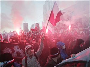 People hold burning flares as they march through  downtown Warsaw  to mark the 95th anniversary of Poland's Independence Day in Warsaw, Poland, today.