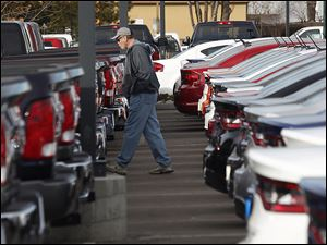 A buyer moves between rows of 2013 Ram pickup trucks and Dart sedans at a Dodge dealership in Littleton, Colo.  Buyers with imperfect credit account for 27 percent of loans for new vehicles.