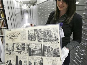 Caitlin McGurk holds up a cartoon from 'Terry and the Pirates' by Milton Caniff at the Billy Ireland Cartoon Library and Museum in Columbus. The museum has more than 300,000 original comic strips from such artists as Charles Schultz and Garry Trudeau.