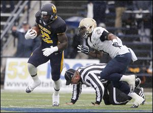A ref is knocked to the ground as UT's David Fluellen is chased by Navy's Lonnie Richardson during game at the University of Toledo Glass Bowl in Toledo, Ohio.