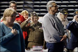 World War II veteran Guadalupe Flores, center, salutes as 'Taps' is played at the conclusion of the ceremony.