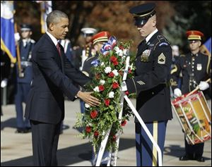 President Obama places a wreath at the Tomb of the Unknowns at Arlington National Cemetery in Arlington, Va., today.