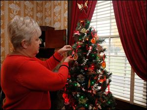 Wolcott House volunteer coordinator Janet Russ Jones, of Maumee, with a dried orange slice that decorates a tree in the parlor. She and other members of the Maumee Garden Club decorated the parlor.