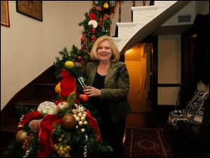 Judy Walrod, next to the banister garland she created.