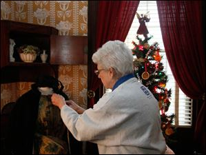 Wolcott House curator Marilyn Wendler, of Perrysburg, adjusts one of the holiday dresses in the parlor.