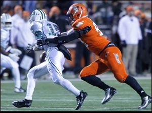 Ohio University quarterback Derrius Vick is chased and sacked by BGSU's Bryan Baird during 2nd half.
