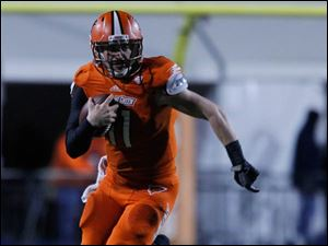 BGSU quarterback Matt Johnson runs with the ball for a first down.
