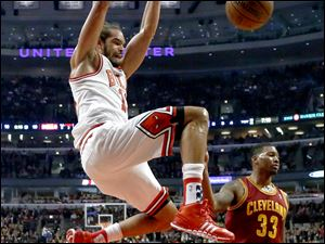 Chicago Bulls center Joakim Noah (13) dunks the ball past Cleveland Cavaliers small forward Alonzo Gee (33) during the first half of an NBA basketball game Monday, Nov. 11, 2013, in Chicago. (AP Photo/Charles Rex Arbogast)