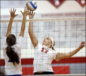 Bedford senior Taylor Purcell, right, hits the ball against  Adrian's Samantha Regalado.
