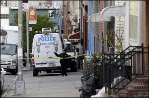 A police officer puts up tape near a crime scene in the Brooklyn section of New York, Monday.  A musician shot and killed two members of an Iranian indie rock band and a third musician early Monday, and wounded a fourth person at their apartment before killing himself on the roof, police and the group's manager said.