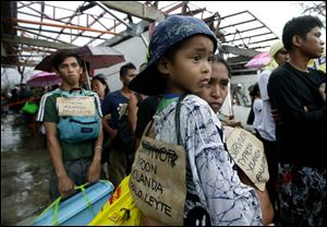 Typhoon survivors hang signs from their necks as they queue up in the hopes of boarding a C-130 military transport plane Tuesday in Tacloban, central Philippines. Thousands of typhoon survivors swarmed the airport on Tuesday seeking a flight out, but only a few hundred made it.