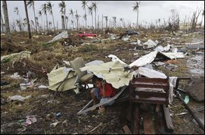 A young survivor uses the remains of some parts of a house to shield him from rain in Tacloban city, Leyte province, central Philippines.