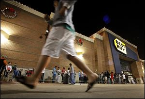 Customers wait in line outside a Best Buy store in Arlington, Texas before midnight on Thanksgiving in 2012. This year the chain's opening time will advance six hours to 6 p.m.  At least a dozen major retailers are planing to welcome customers on Thanksgiving Day.