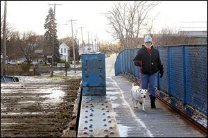 Ammy Matthews, of South Toledo walks her 5-year-old 'pit bull,' Ava, over a bridge to visit her grandfather. Council voted to raze the bridge spanning railroad tracks in the city's Old South End.