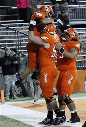 Heath Jackson, left, Logan Deitz, and David 'Chief' Kekuewa celebrate Jackson's 32-yard reception for a touchdown.