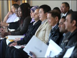 Faithful Famogun, left, leans forward to listen to a speaker address herself and other new citizens.