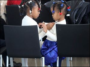 Miyonnah Gordon, 6, left, and her sister Serinity, 3, right, help one another button their sweaters. Thirty eight new citizens, including the girls' mother Kymaeh Brisbane Gordon, were sworn in during the ceremony.