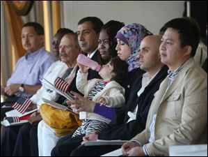 Rana El Khatib, center, holds her daughter, Mira Moussa, 1, as she and other new citizens listen to guest speakers.