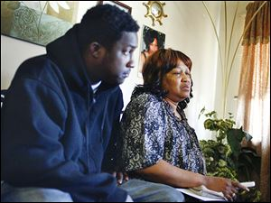 Ann Quinn, mother of Jomar Quinn, sits with Juan Kane and other family and friends at her apartment in Toledo on Wednesday. Jomar