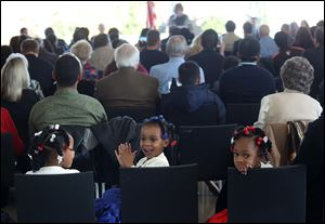 Miyonnah Gordon, 5, left, and her sisters Serinity, 3, and Mariah, 5, sit together during the naturalization ceremony. The girls' mother, Kymaeh Brisbane Gordon of Liberia, took her oath.