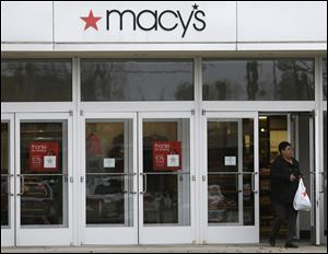 A woman walks out of Macy's department store in University Heights, Ohio, Monday.