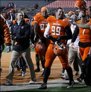 BGSU head football coach Dave Clawson exits the field with his team after defeating Ohio University.