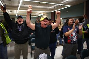 Boeing machinists react as the results of a vote are read at the International Association of Machinists union hall in Seattle. Boeing machinists in the Northwest rejected a contentious contract proposal Wednesday that would have exchanged concessions for decades of secure jobs.