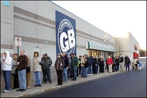 Customers wait outside Gabriel Brothers, stretch-ing almost to Target, for the grand opening of the company's first store in the Toledo area on Thursday. The discount retailer on Monroe Street in Sylvania Township offers a variety of products, from clothing to greeting cards and more.