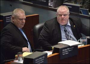 Mayor Rob Ford and his brother Councillor Doug Ford, left, attend city council in Toronto on Wednesday.