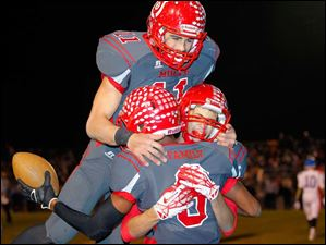 Bedford players Alec Hullibarger (11) Trent Santiago (86) and Collin Carter (8) celebrate Carter's touchdown.