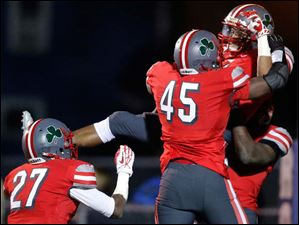 Central Catholic's Marcus Winters (5) celebrates his pick six touchdown with teammates Chris Green (45) and Tejuan James (27).