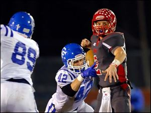 Bedford High School quarterback Brad Boss (2) has the ball stripped by Detroit Catholic Central player Ryan McGillivary (42) during the second quarter.