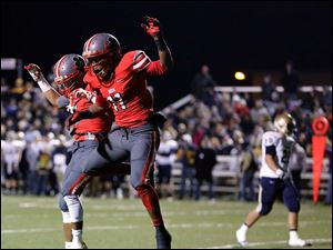 Central Catholic's Jermiah Braswell (11) celebrates scoring a touchdown against Tiffin Columbian with teammate Marcus Winters (5).