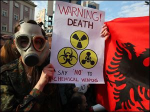 An Albanian student wears a gas mask and holds a sign  during a protest against chemical weapons during a  protest against the dismantling of Syrian chemical weapons in Albania in front of the Prime Minister's office in Tirana  Thursday.