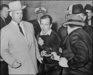Lee Harvey Oswald, assassin of President John F. Kennedy, reacts as Dallas night club owner Jack Ruby, foreground, shoots him at Dallas police headquarters on Nov. 24, 1963. At left is Detective Jim Leavelle.