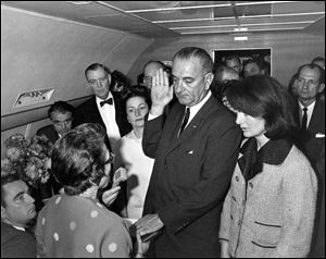 Lyndon B. Johnson is sworn in as president as Jacqueline Kennedy stands at his side in the cabin of the presidential plane on the ground at Love Field in Dallas. Judge Sarah Hughes, a Kennedy appointee to the federal court, left, administered the oath.