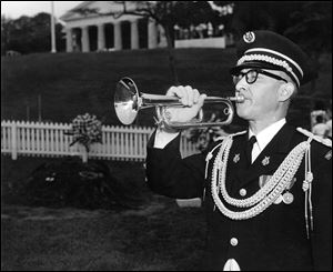 Army bugler Keith Clark, who played taps during John F. Kennedy's funeral, plays the bugle at Mr. Kennedy's grave in 1964, a year after the president's assassination.