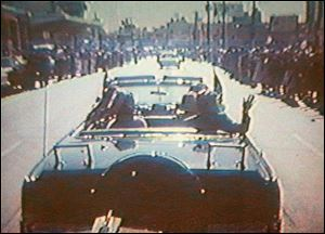 Footage taken by presidential aide Dave Powers and photographed from a television screen shows President John F. Kennedy, accompanied by his wife, Jacqueline, waving to the crowd in Dallas on Nov. 22, 1963.
