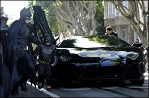 Miles Scott, dressed as Batkid, second from left, exits the Batmobile with Batman to save a damsel in distress in San Francisco today.