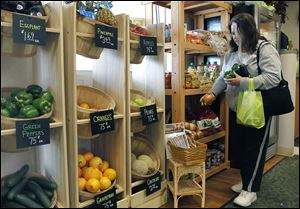 Cindy Thomas of Toledo shops for vegetables at the Flower Market's Garden Grocer on Monroe Street.
