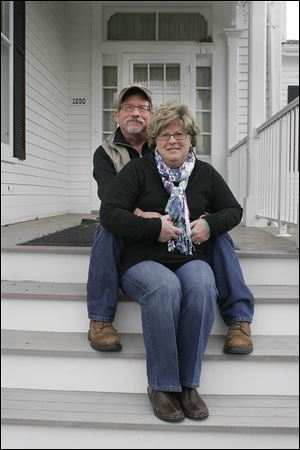 Bill and Leslie Nestor of Marblehead, Ohio, sit on the steps of the property they got for a bid of $710,000. They said they plan to move in to Castalia Farms.